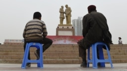 China - TO GO WITH CHINA-XINJIANG-UNREST-MIGRATION-POPULATION BY BENJAMIN HAAS This photo taken on April 16, 2015 shows a Uighur man and boy watching a performance under a statue of late communist leader Mao Zedong meeting with a Uighur, in the central