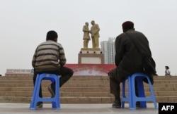 """Отец и сын, уйгуры, в центре местной столицы Урумчи смотрят на огромную статую """"Мао встречает уйгура"""""""