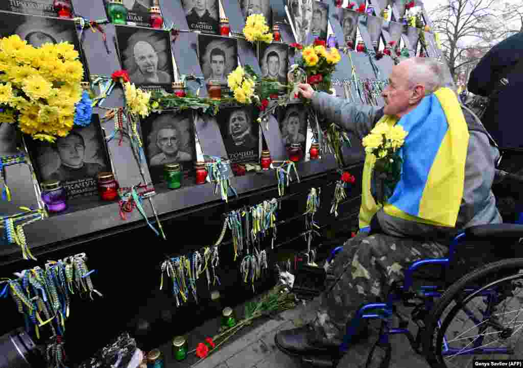 Kiýew, Ukrain rewolýusiýasynyň başlanmagynyň bäş ýyllygyna gabat wepat bolan Maýdan aktiwistleriniň ýadygärliginde gül goýýan adam. 21-nji noýabr. (AFP/Genya Savilov)