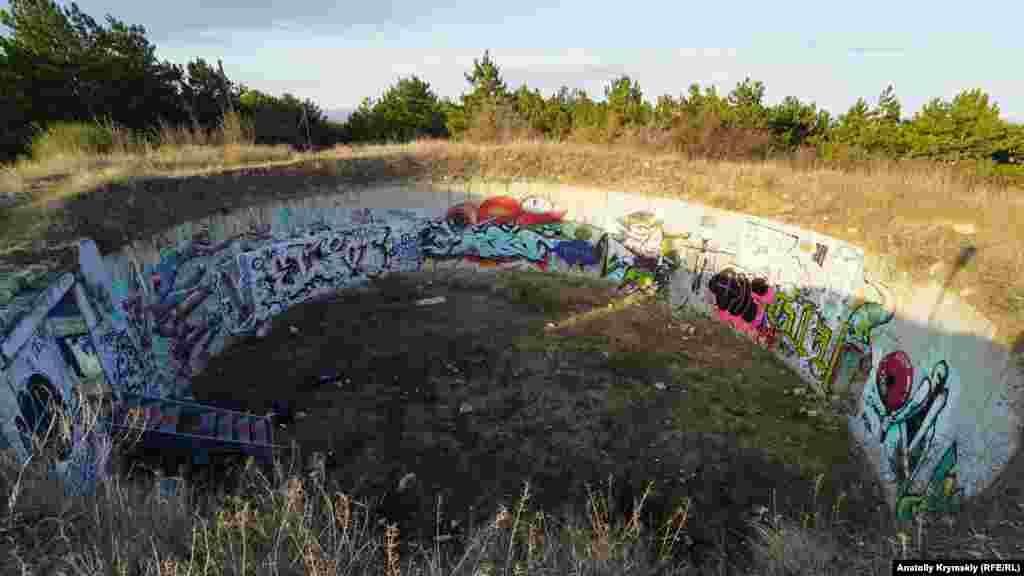 Раньше на этом месте размещался пожарный водоем. Теперь там «углубились» в свое творчество местные мастера граффити