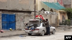 A man fills his car with personal belongings as families leave insecure neighborhoods in the flashpoint city of Fallujah.