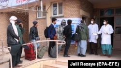 Afghan health officials screen people entering Afghanistan from Iran at the border in Herat Province last month.