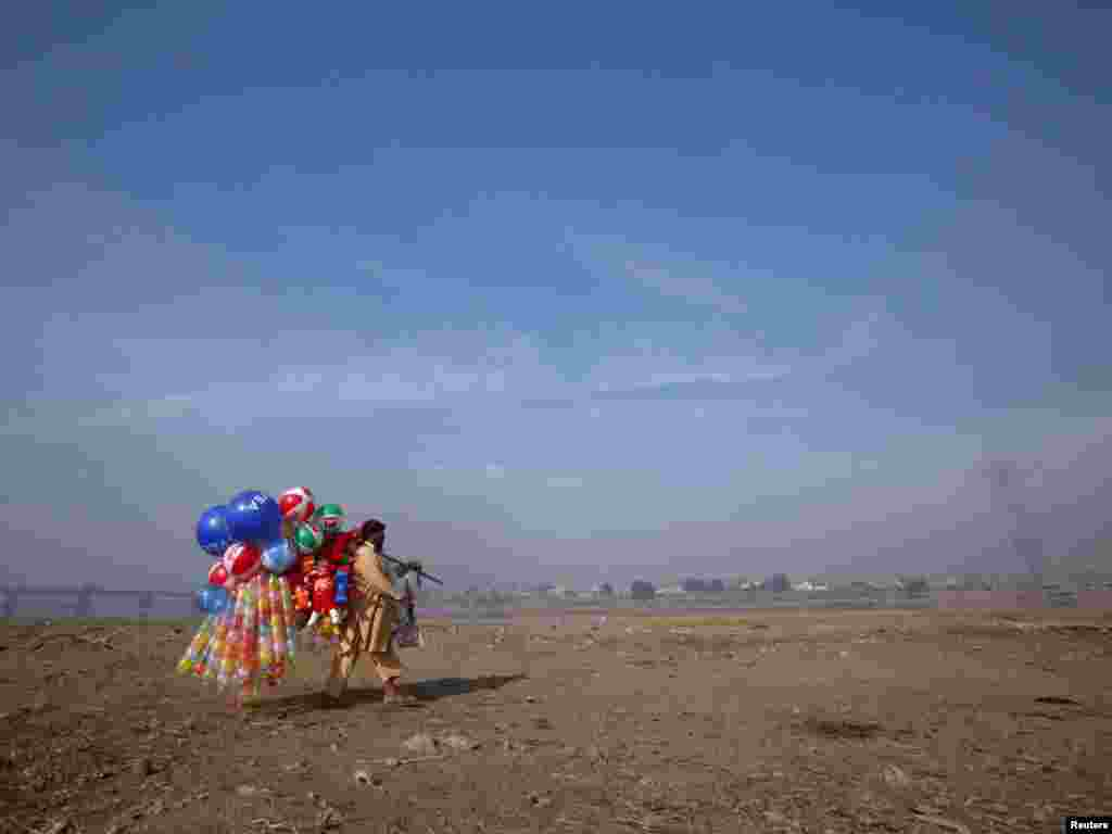 A man carries balloons for sale near the banks of the Ravi River in Lahore, Pakistan, on November 14. (REUTERS/Mohsin Raza)