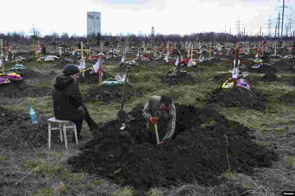 A gravedigger works as his wife watches at a cemetery in Donetsk, Ukraine, where workers killed by a blast at the Zasyadko coal mine will be buried. Thirty-three miners were confirmed dead. Mine officials said the explosion was most likely caused by gas and not fighting in the war between Moscow-backed rebels and Ukraine government forces. (Reuters/Marko Djurica)
