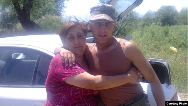 Armenia - Soldier Hakob Injighulian poses for a photograph with his mother during military service.