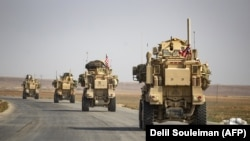 U.S. military vehicles drive on a road after U.S. forces pulled out of their base in the Northern Syrian town of Tal Tamr, October 20, 2019