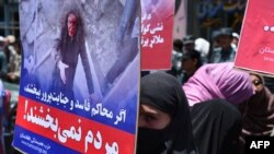 An Afghan woman carries a placard of Afghan woman Farkhunda, 27, who was lynched by an angry mob, during a protest held by the Solidarity Party of Afghanistan in Kabul in July 2015.