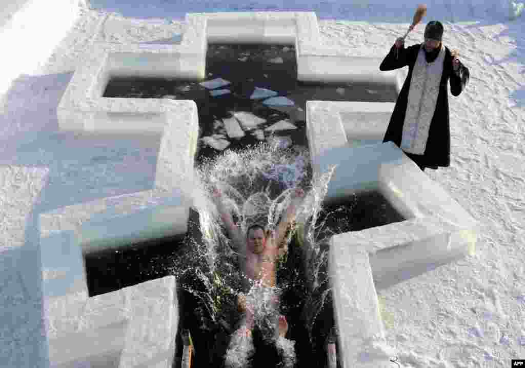 A believer plunges into icy waters in Pilnitsa, Belarus as an Orthodox priest blesses him on the eve of Epiphany. (AFP/Viktor Drachev)
