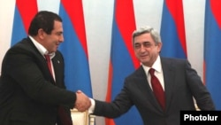 Armenia -- Prosperous Armenia Party leader Gagik Tsarukian (L) and President Serzh Sarkisian sign a joint declaration pledging support for the latter's reelection bid, 17Feb2011.