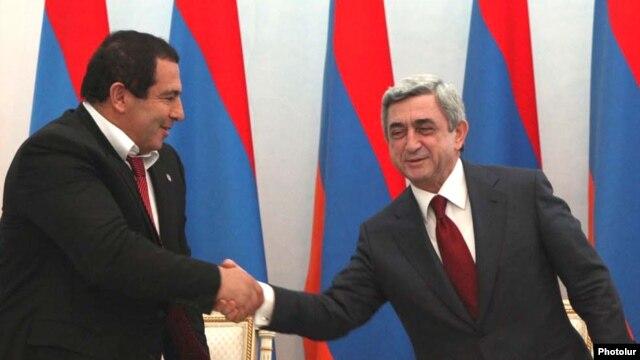 Armenia -- Prosperous Armenia Party leader Gagik Tsarukian (L) and President Serzh Sarkisian sign a joint declaration pledging support for the latter's reelection bid, 17Feb2011.