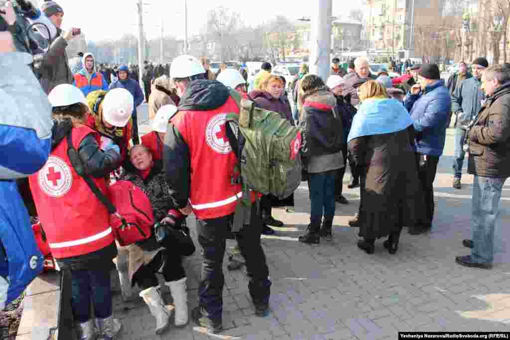 Жінку оглядають волонтери загону швидкого реагування Червоного Хреста у Запоріжжі. З місця події її забрала швидка з підозрою на перелом ноги