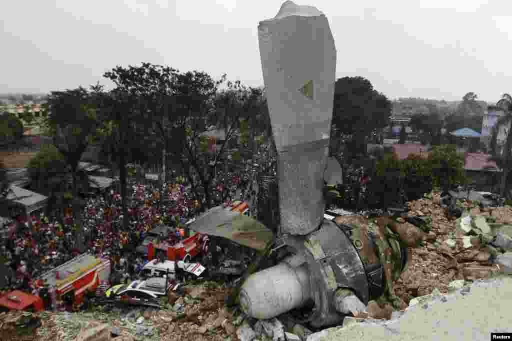 A propeller from an Indonesian military C-130 Hercules transport plane rests on the roof of a building after the plane crashed on June 30 into a residential area in the North Sumatra city of Medan, Indonesia. More than 100 are feared dead. (Reuters/Roni Bintang)