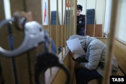 Karaulova covers her face from photographers in a Moscow courtroom on December 1.
