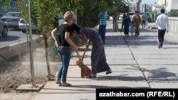 Türkmenistanda köçeleri süpürmek we arassalamak işlerine gatnaşýan edara-kärhanalaryň işgärleri. Arhiwden alnan surat.