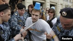"Officers detain a ""blue bucket"" activist in Moscow on May 2."