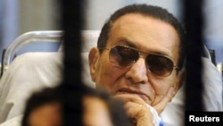 Former Egyptian President Hosni Mubarak sits inside a cage in a courtroom at the police academy in Cairo on April 13.