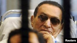 Former Egyptian President Hosni Mubarak sits inside a cage during a court hearing earlier this year.