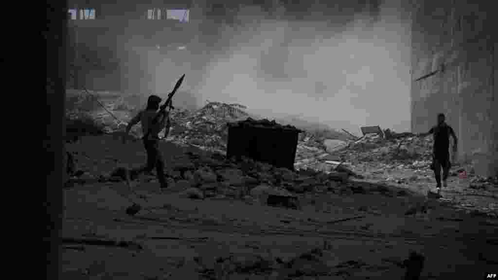 A Syrian rebel fighter carrying a rocket-propelled grenade moves across open ground under heavy tank fire from Syrian government forces during an intense battle in the al-Arqub neighborhood of Aleppo on September 26. (AFP/Zac Baillie)