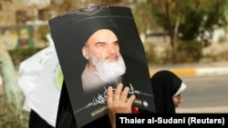 An Iraqi Shi'ite Muslim woman holds a picture of Iran's late leader Ayatollah Ruhollah Khomeini during a parade marking the annual al-Quds Day, (Jerusalem Day) on the last Friday of the Muslim holy month of Ramadan in Baghdad, June 8, 2018
