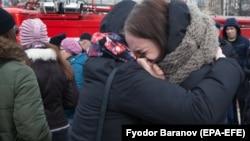 Плачущие женщины рядом со сгоревшим торговым центром в Кемерове. 27 марта 2018 года.