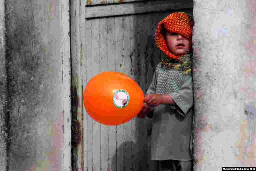An Afghan boy plays with a balloon distributed by a polio vaccination team during a vaccination campaign in Kandahar. Kandahar has seven new polio cases detected in 2018. Afghanistan is one of two countries -- along with neighboring Pakistan -- where polio is still endemic, crippling hundreds of children every year. (epa-EFE/Muhammad Sadiq)