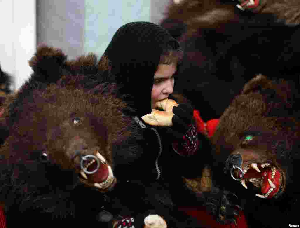 A girl sits among costumes made from bearskins after performing a dance in the town of Comanesti, Romania. People from this region follow a pre-Christian rural tradition in which they sing and dance to ward off evil. (Reuters/Stoyan Nenov)