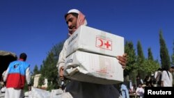 Житель Афганистана с коробками с помощью от Международной Федерации Обществ Красного Креста и Красного Полумесяца (МФКК и КП). Иллюстративное фото.