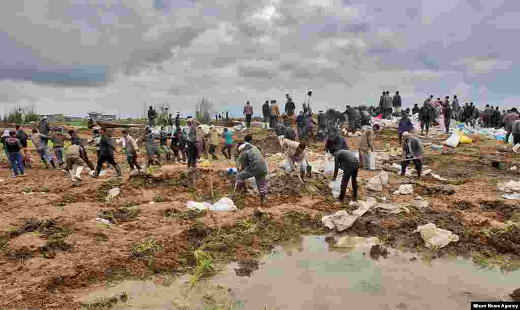 Rescue workers dig through the mud in Aq Qala.