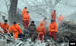 Rescuers sift through the wreckage at the crash site near the Manas airport on January 17. Eyewitnesses say looting broke out almost as soon as police and emergency workers arrived on the scene.