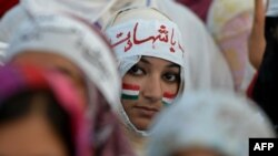 Pakistani supporters of Tahir-ul-Qadri listen to their leader's speech in front of the Parliament during an anti-government protest in Islamabad on August 28, 2014.
