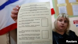 An election commission official shows a ballot paper for the referendum at a polling station in Simferopol on March 15.