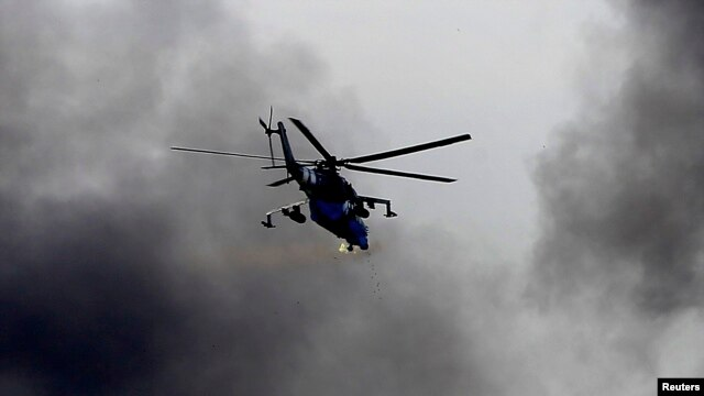 A Ukrainian Mi-24 gunship fires its cannons at rebels at the main terminal building of Donetsk airport on May 26.