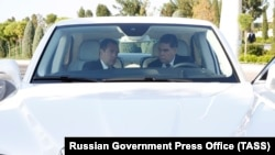 Medvedev and Berdymukhammedov sit inside a Russian-made limousine at the Caspian Economic Forum.