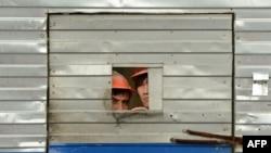Мигранты смотрят через окно в ограждении на строительстве. Москва, 24 мая 2013 года.