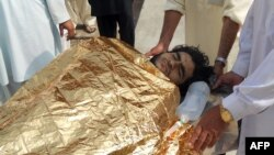Men carry a bombing victim into a hospital following an attack on the home of militant commander Mullah Nabi Hanafi in northwestern Pakistan.
