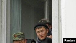 Сотрудники силовых структур наблюдают за уличными беспорядками из здания областной администрации в Оше.