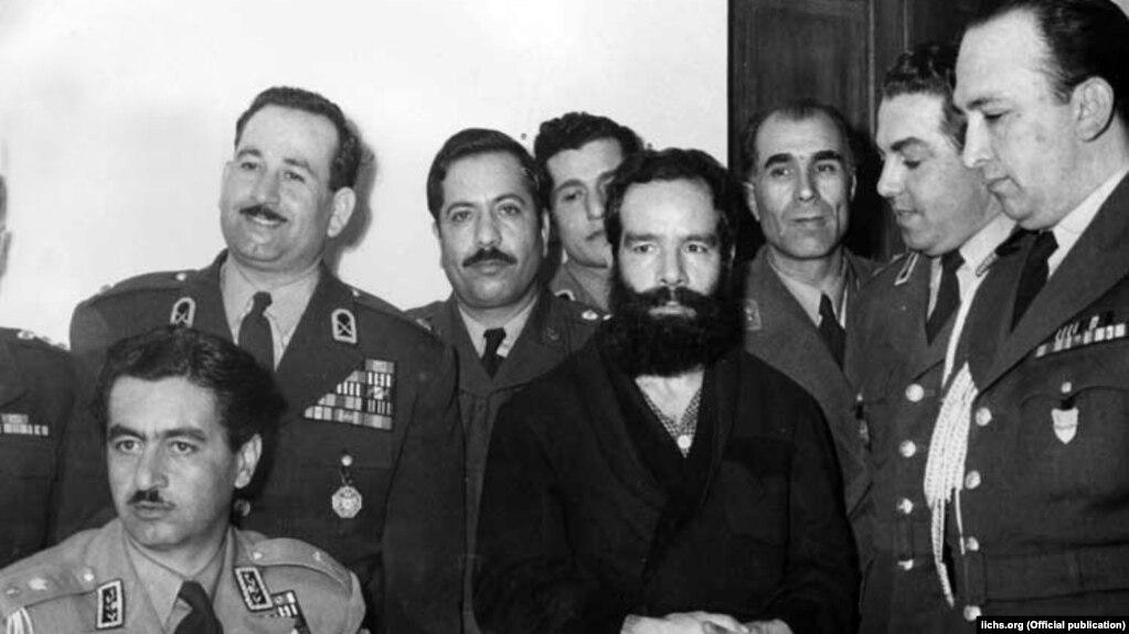 حسین فاطمی (در میانه تصویر) اندکی پس از بازداشت توسط نیروهای تیمور بختیار (نشسته، چپ) فرماندار نظامی وقت تهران