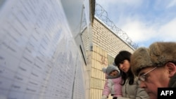 Relatives of demonstrators detained during a mass rally protesting the reelection of President Alyaksandr Lukashenka check a list of prisoners outside a prison in Minsk on December 21.