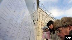 Listele cu persoanele arestate în fața unei închisori de la Minsk