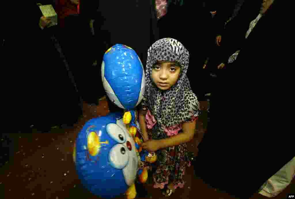 An Iraqi girl holds a balloon as children receive gifts donated to the families of fighters of the Popular Mobilisation units ahead of the Eid al-Fitr festivities in Najaf on July 13. (AFP/Hajdar Hamdani)