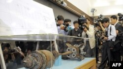 Cameramen take footage of torpedo parts salvaged from the Yellow Sea during a press conference at the Defense Ministry in Seoul on May 20.