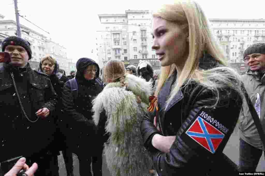 """Жалғыз адамдық пикеттер өткен күні ол маңда """"Новороссия"""" деген жазуы бар белгі тағып, Георгий лентасын байлаған адамдар да жүрді. Мәскеу, 19 сәуір 2015 жыл."""