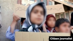 "A child without citizenship In Iran holds a placard saying ""I don't have an ID"". Undated"
