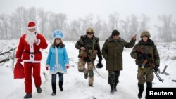 Local residents dressed as Father Frost and his granddaughter Snegurochka (Snow Maiden) walk with servicemen as they visit checkpoints of the Ukrainian Army and self-defense units to help welcome in the near year near Lysychansk in the Luhansk region. (Reuters)