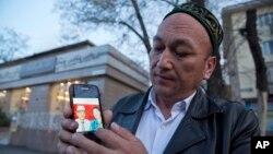 Казак жараны Омир Бекалы Кытайдагы саясий лагерде деген ата-энесинин сүрөтүн көрсөтүп жатат.