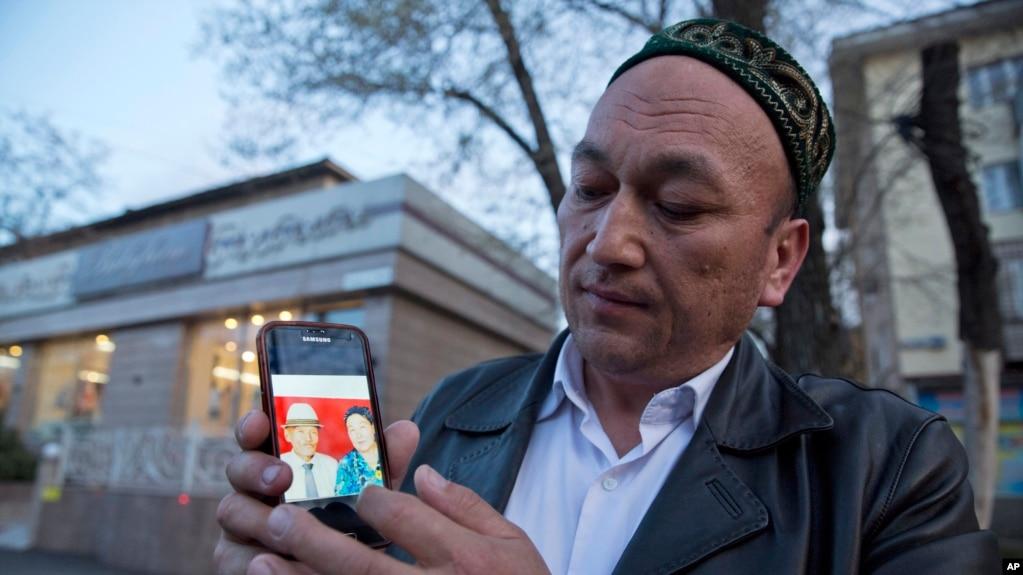Казах из Китая показывает фотографии своих родственников, которые, по его словам, задержаны властями