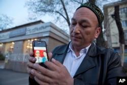 """Өмірбек Бекалы Шыңжаңдағы """"саяси тәрбиелеу лагерінде"""" отырған туыстарының суреттерін көрсетіп тұр. Алматы, 31 наурыз 2018 жыл."""