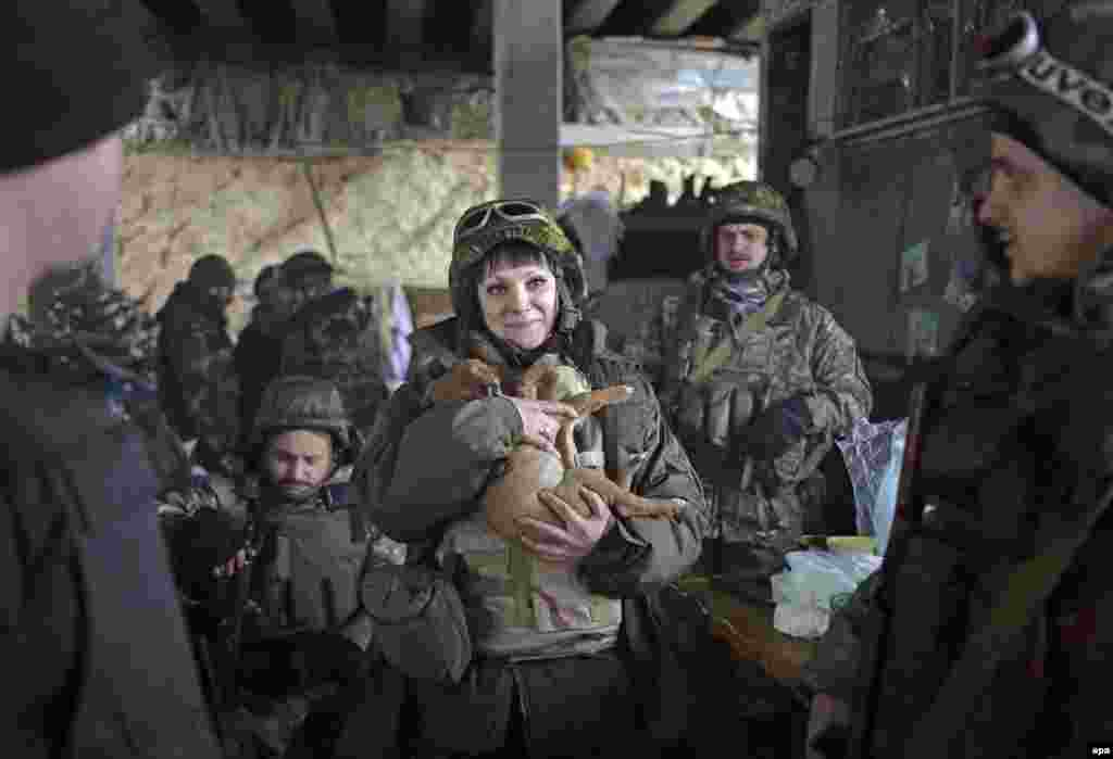 A female Ukrainian soldier holds a dog at a checkpoint in the village of Pesky near Donetsk.