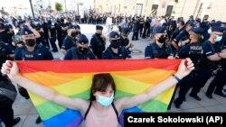 Egy nő szivárványos zászlót tart a szélsőjobboldali aktivisták tüntetése ellen Varsóban, 2020. augusztus 16-án.