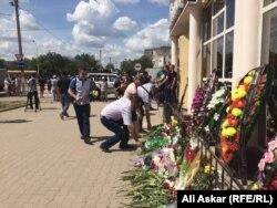 Жители Актобе несут цветы к зданию оружейного магазина, где произошло одно из первых убийств 5 июня. Актобе, 8 июня 2016 года.